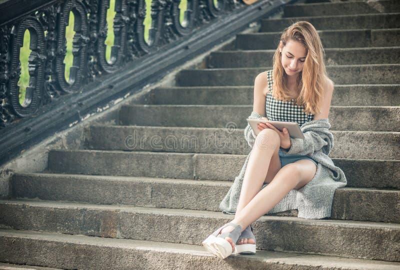 Meisje die een digitale tablet in openlucht gebruiken stock foto's