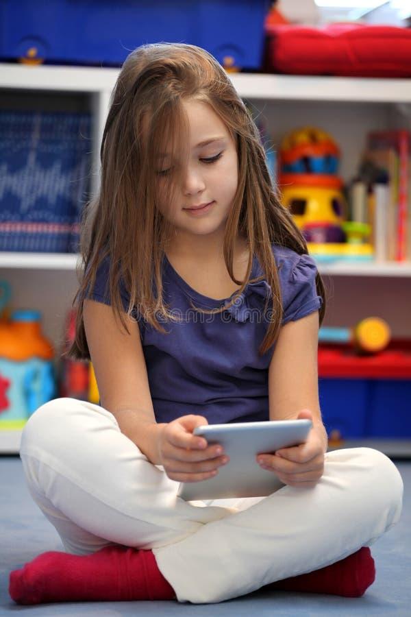 Meisje die een digitale tabletcomputer met behulp van stock afbeelding