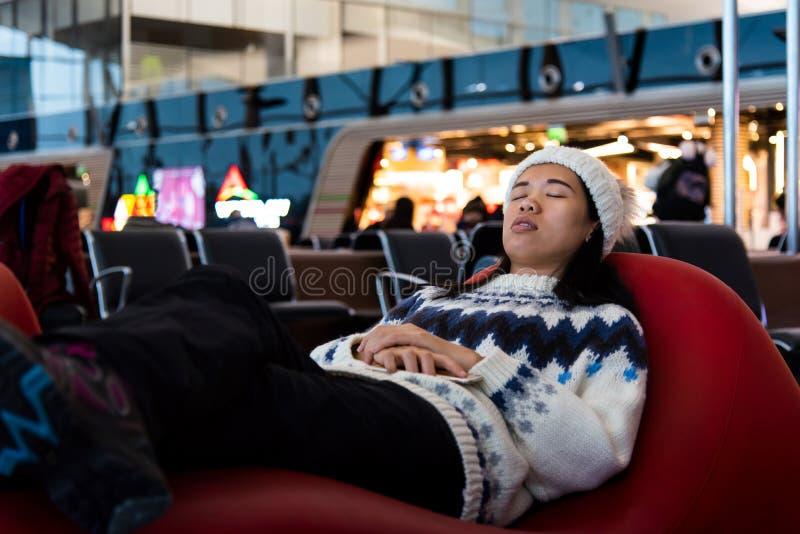 Meisje die een dutje nemen terwijl het wachten bij de luchthaven stock afbeeldingen