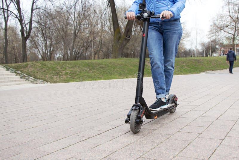 Meisje die een elektrische autoped in de parkweg berijden met een actiecamera Technologisch milieuvriendelijk vervoer modern stock afbeeldingen