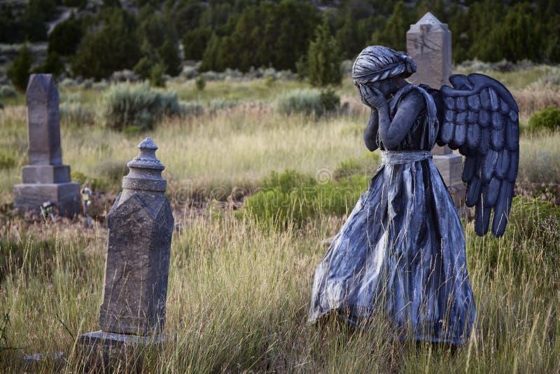 Meisje die een engelenkostuum in een oude ernstige werf dragen stock afbeelding