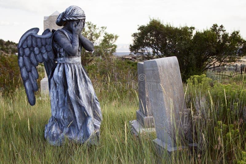 Meisje die een engelenkostuum in een oude ernstige werf dragen stock afbeeldingen