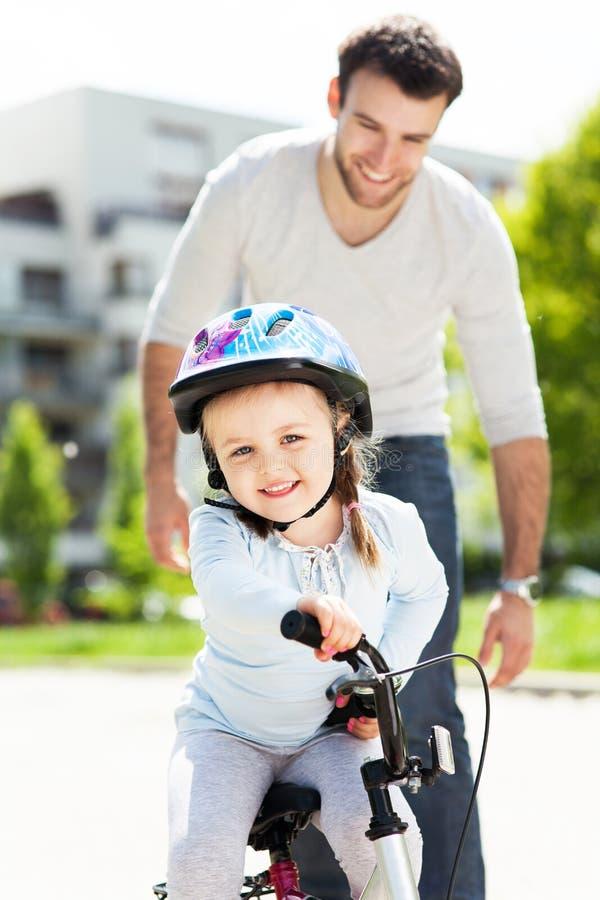 Meisje die een fiets met haar vader leren te berijden royalty-vrije stock afbeelding
