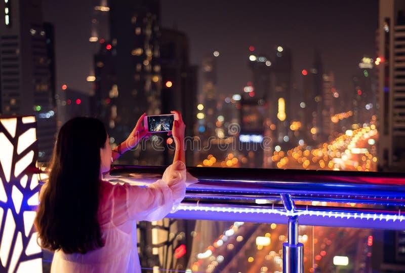 Meisje die een foto van cityscape van Doubai nemen stock foto's