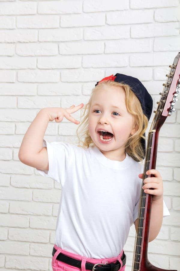 Meisje die een gitaar en het zingen houden royalty-vrije stock afbeeldingen