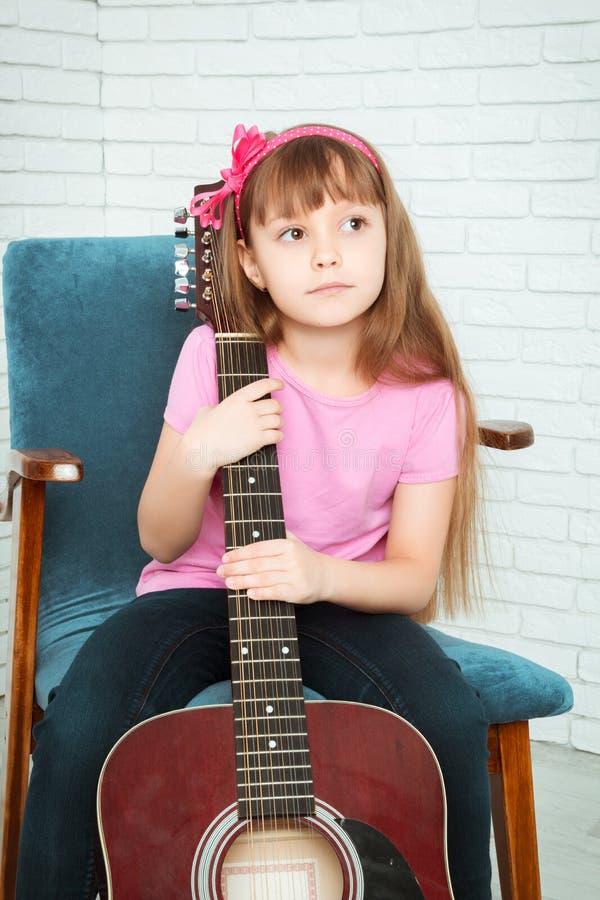 Meisje die een gitaar koesteren royalty-vrije stock foto