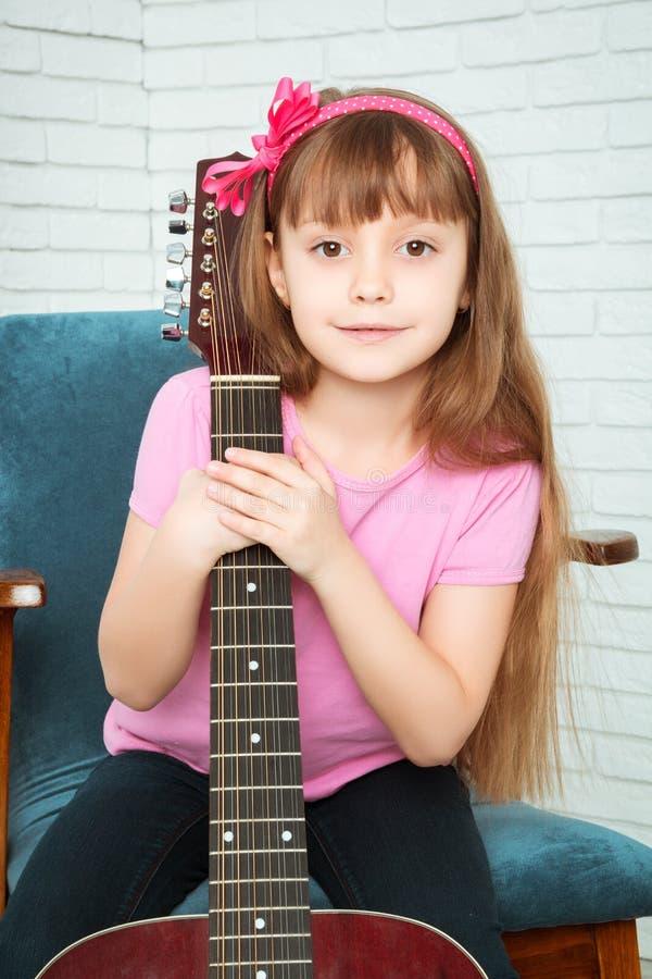 Meisje die een gitaar koesteren royalty-vrije stock afbeeldingen