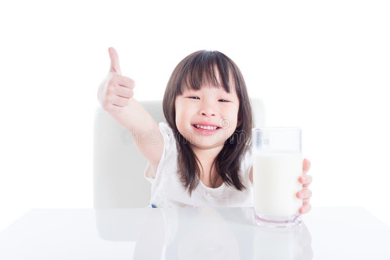 Meisje die een glas melk houden en duim tonen stock foto's