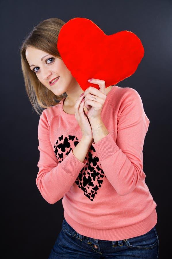 Meisje die een hart op een zwarte achtergrond houden stock afbeeldingen