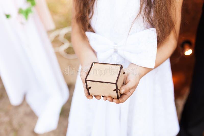 Meisje die een houten doos in haar handen, een doos voor ringen houden stock foto's