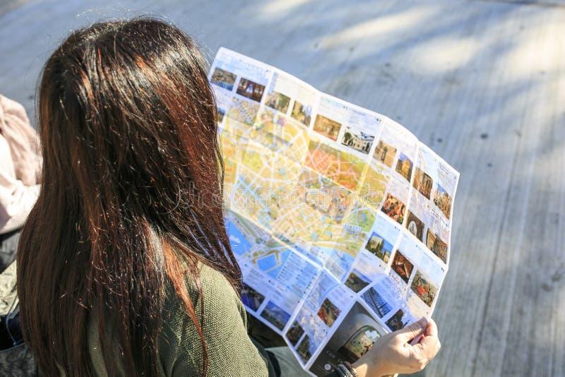 Meisje die een kaart in de straat kijken royalty-vrije stock afbeeldingen