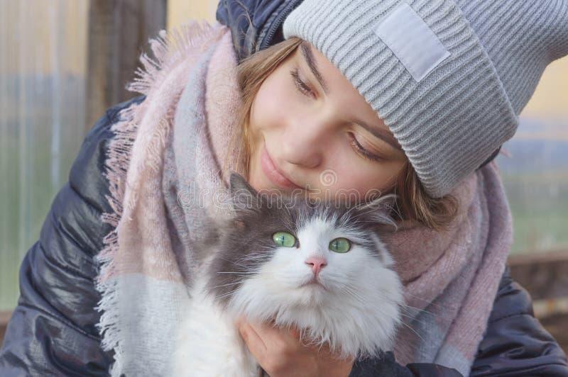 Meisje die een kat met groene ogen koesteren stock fotografie