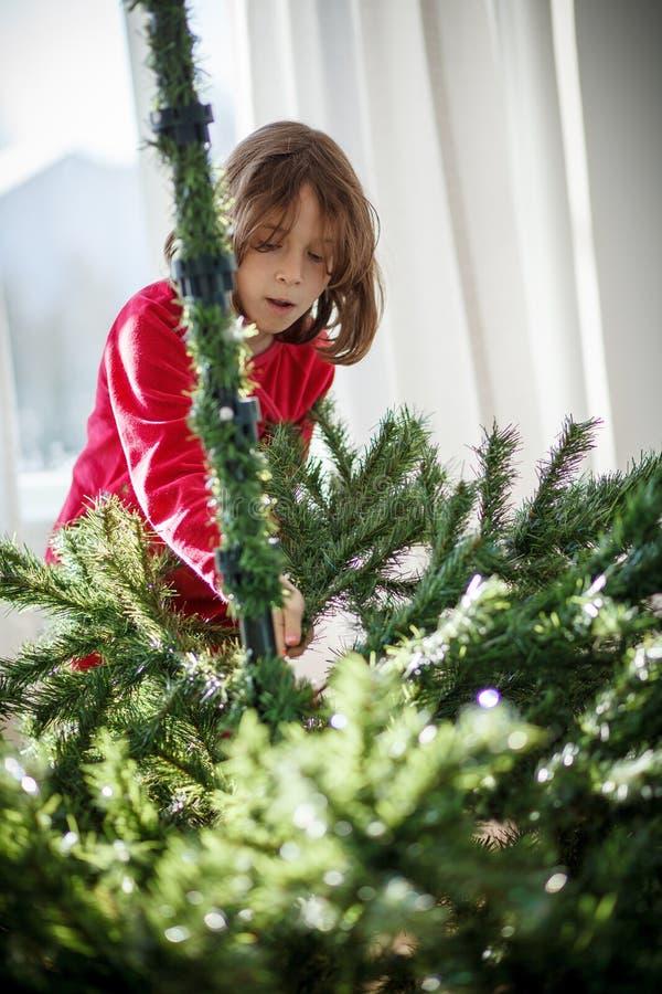 Meisje die een Kerstboom verfraaien stock foto's
