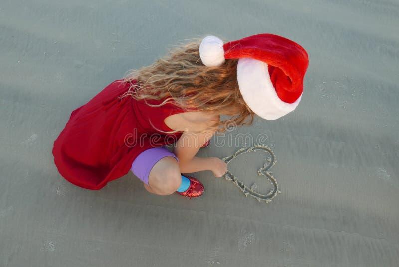 Meisje die een Kerstmanhoed dragen die een hart in het zand trekken bij het strand stock foto