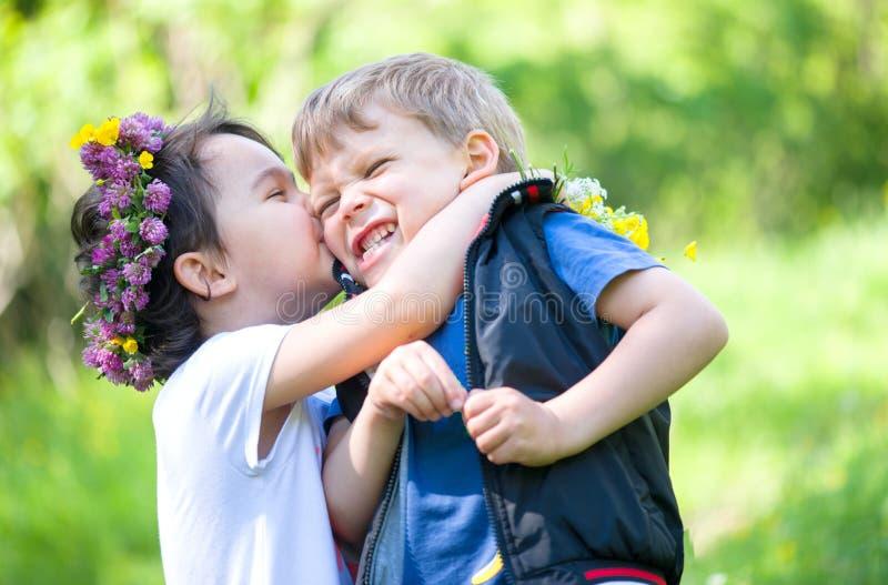 Meisje die een kleine jongen in de zomertijd kussen royalty-vrije stock fotografie