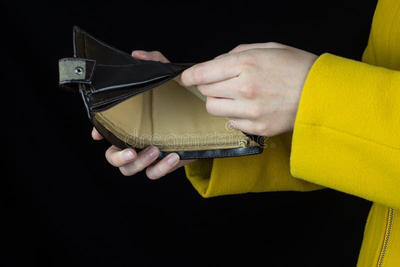 Meisje die een lege beurs in handen houden, close-up, zwarte achtergrond, beurs royalty-vrije stock afbeeldingen