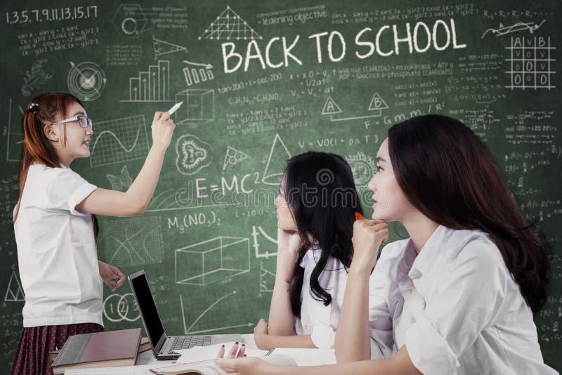 Meisje die een les verklaren bij haar vrienden royalty-vrije stock afbeelding