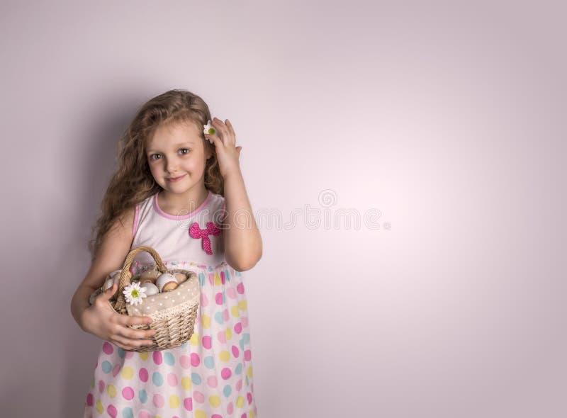 Meisje die een mand met paaseieren en bloemen houden stock foto