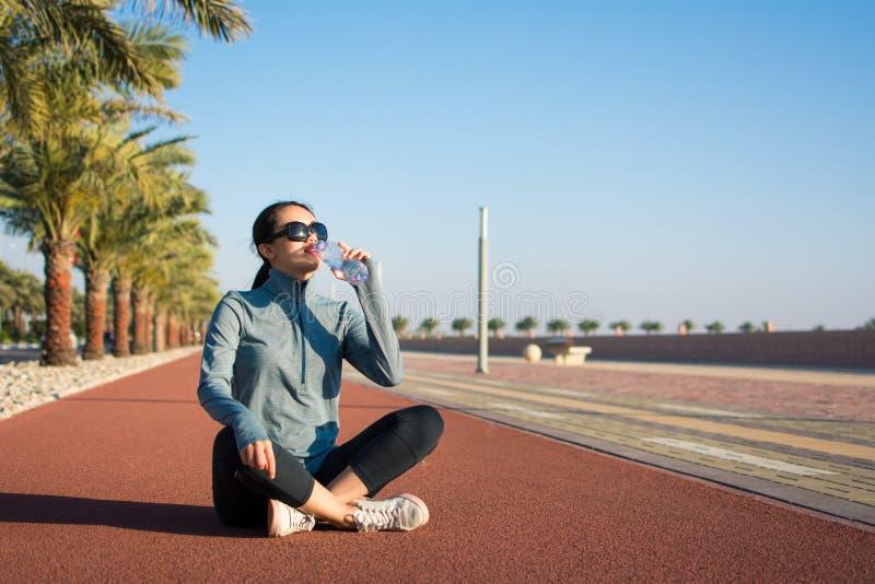 Meisje die een onderbreking van training op renbaan nemen royalty-vrije stock foto