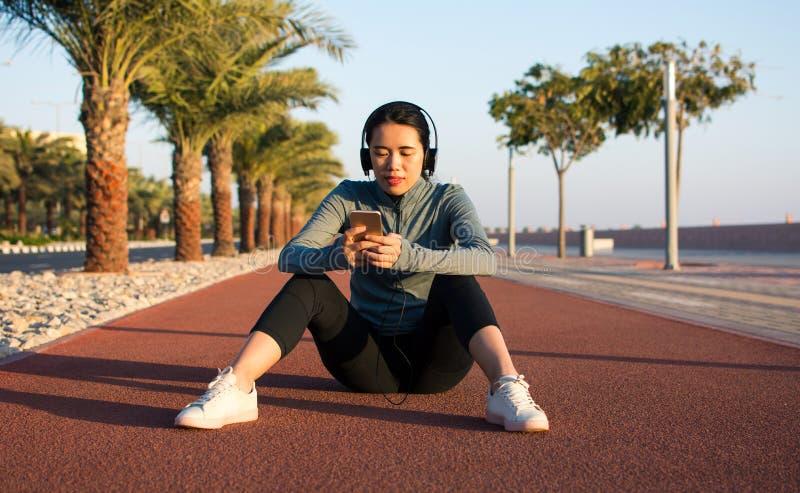 Meisje die een onderbreking van training op renbaan nemen stock fotografie