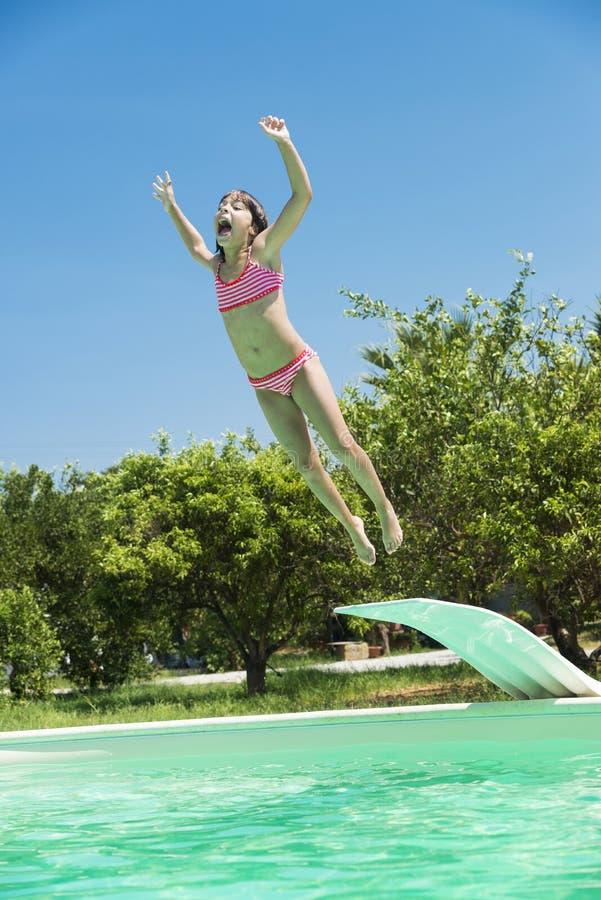 Meisje die in een openluchtpool springen stock afbeelding