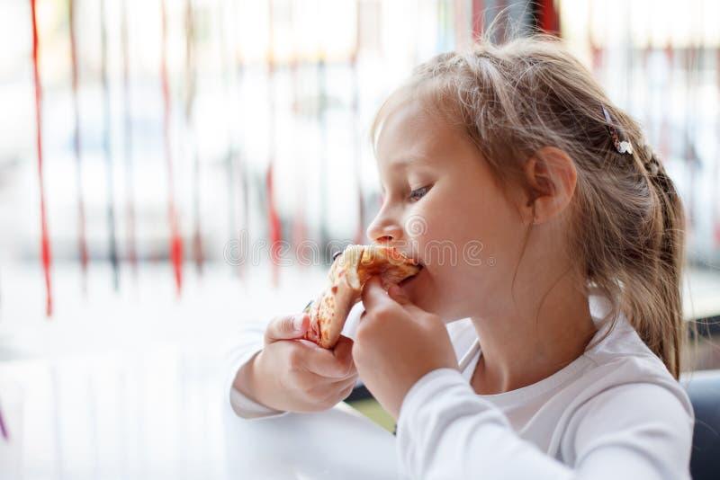 Meisje die een pizza in koffie eten royalty-vrije stock fotografie