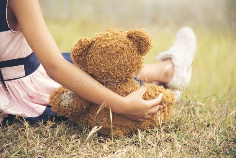 Meisje die een pluizige teddybeer koesteren stock afbeeldingen