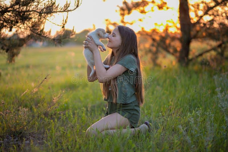 Meisje die een puppy en het glimlachen van Labrador houden Bij zonsondergang op een bosopen plek in de lente Vriendschap, geluk stock afbeelding