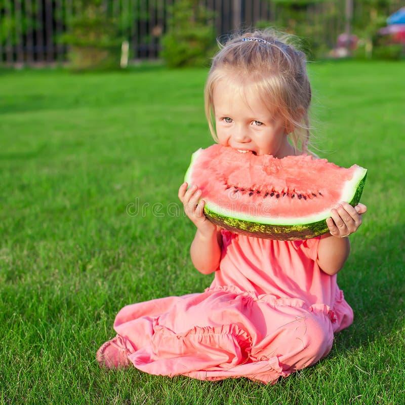 Meisje die een rijpe sappige watermeloen binnen eten royalty-vrije stock afbeeldingen