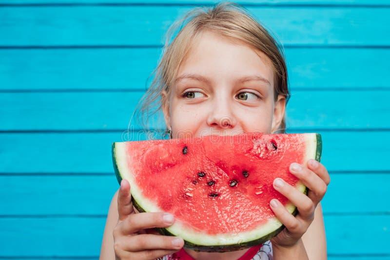 Meisje die een rijpe sappige watermeloen over de blauwe achtergrond van de plankmuur eten royalty-vrije stock foto's