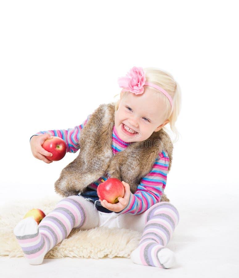 Meisje die een rode appelzitting op de vloer houden stock afbeelding