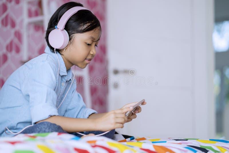 Meisje die een smartphone gebruiken om te luisteren muziek royalty-vrije stock fotografie