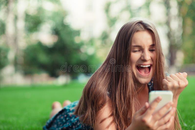Meisje die een smsbericht met goed nieuws in een mobiele telefoon ontvangen stock afbeelding
