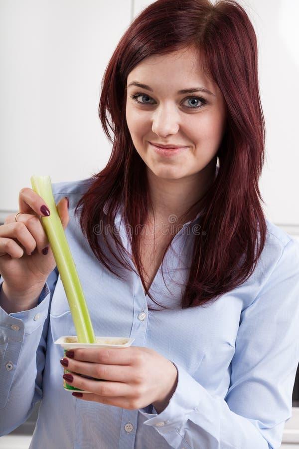 Meisje die een stok van selderie eten stock foto