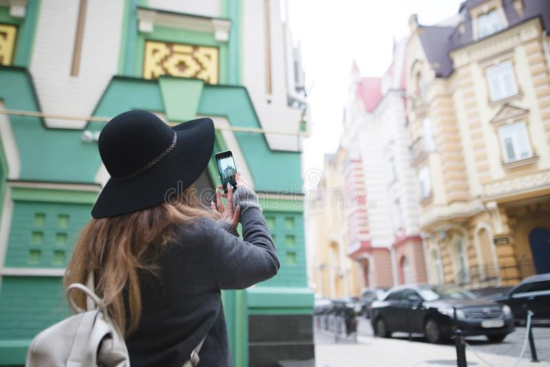 Meisje die een straatfoto op de telefoon fotograferen Een toeristenmeisje maakt een foto van architectuur op een smartphone stock fotografie