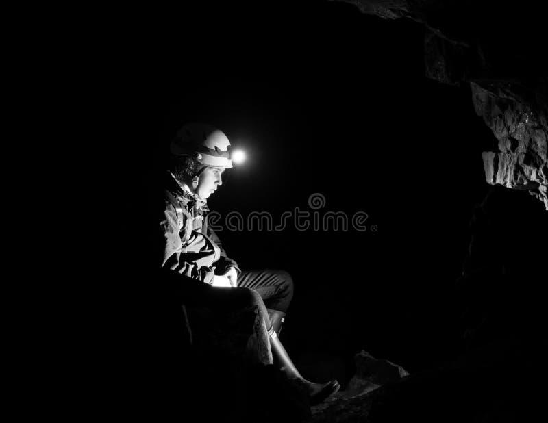 Meisje die in een verlaten mijn met licht van hoofdtoorts rusten stock afbeeldingen