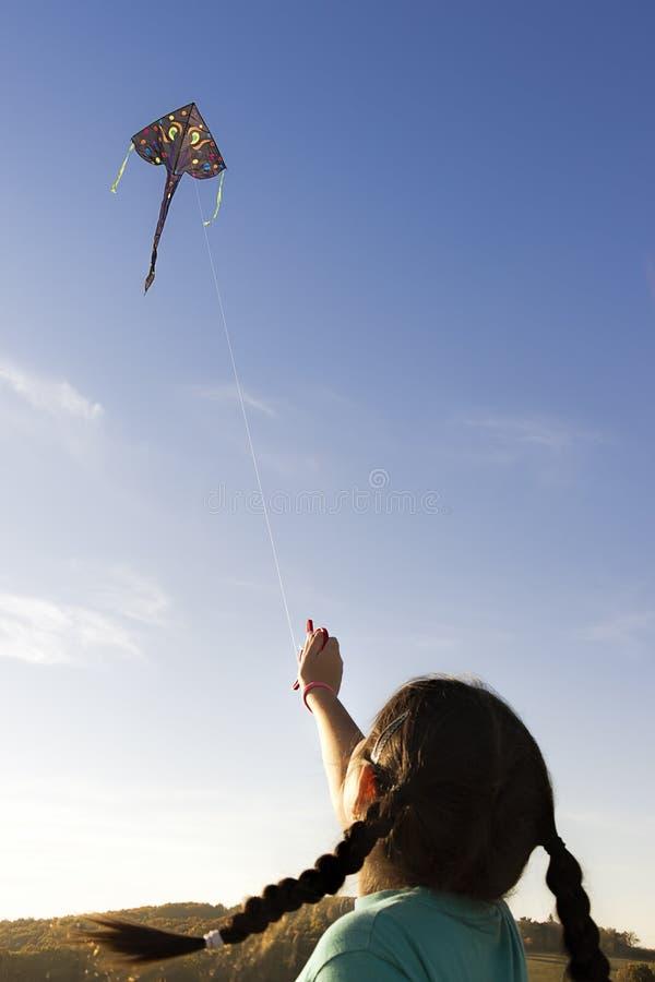 Meisje die een vlieger in de hemel vliegen stock afbeelding