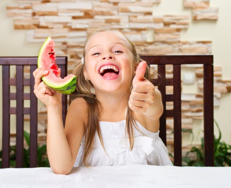 Meisje die een watermeloen eten stock foto