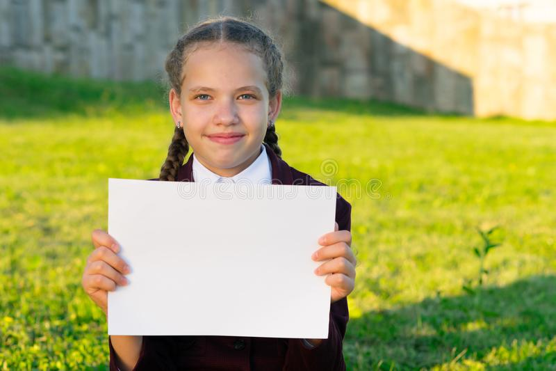 Meisje die een wit blad van document in een park op de straat houden royalty-vrije stock afbeeldingen