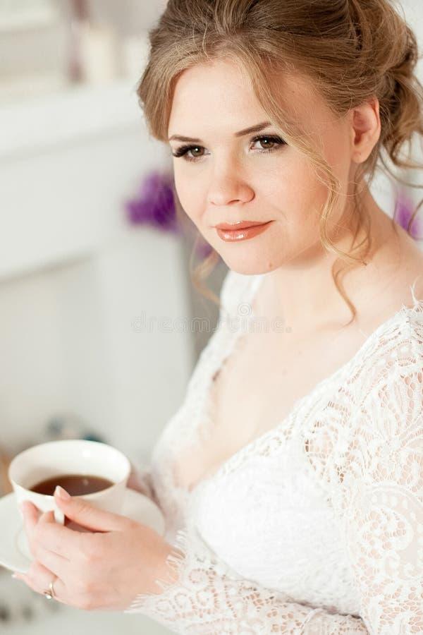 Meisje die een witte koffiemok houden In een witte laag Koffie in bed De ochtend begint met koffie royalty-vrije stock afbeeldingen