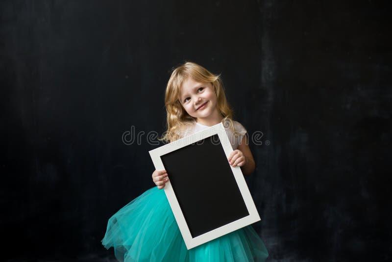 Meisje die een zwart schoolbord met lege lege ruimte voor u houden royalty-vrije stock afbeelding