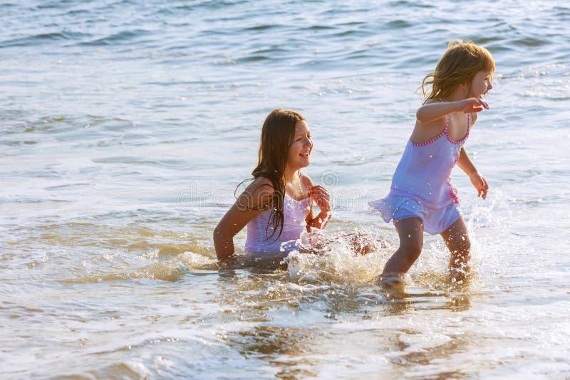 Meisje die en de oceaan in de grote golven op strand spelen springen stock foto's