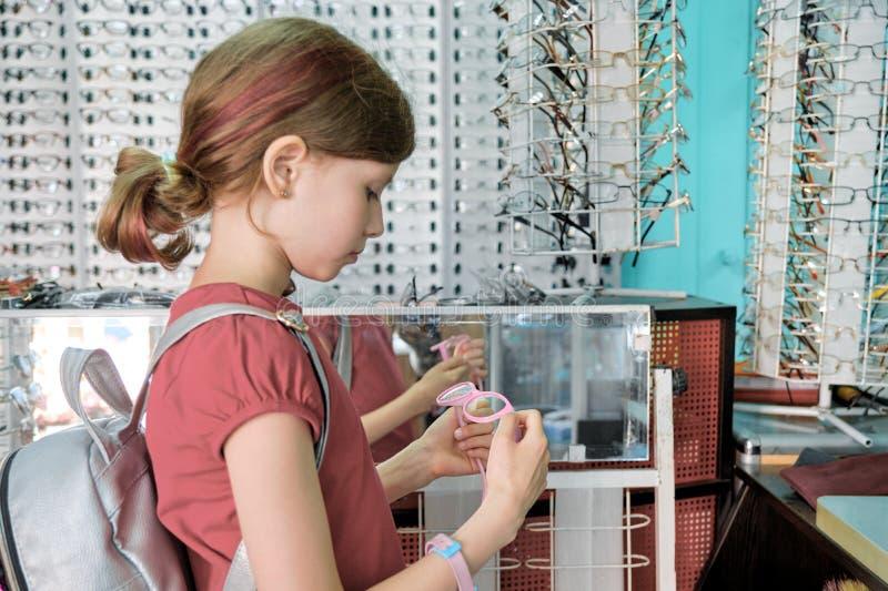 Meisje die en glazen, kind dichtbij winkelvenster kiezen in eyewear opslag kijken royalty-vrije stock fotografie