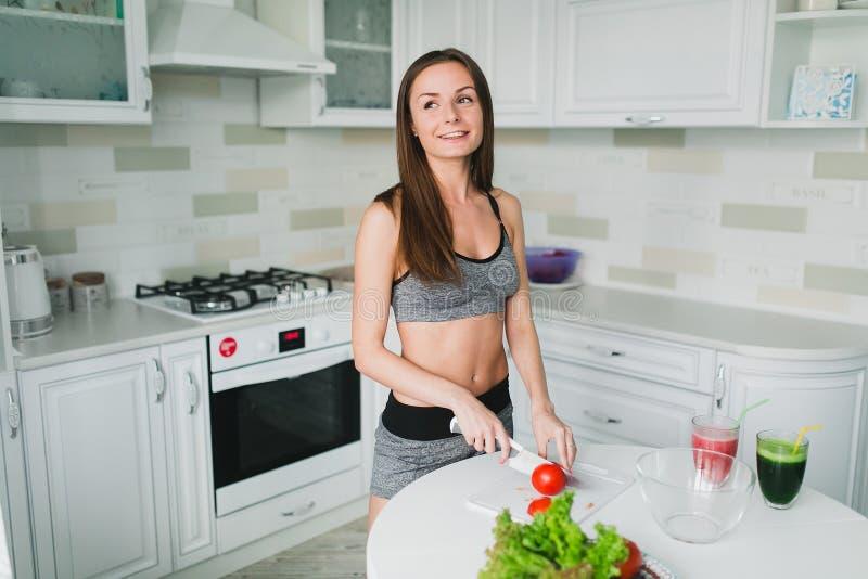 Meisje die en salade in de keuken voorbereiden eten stock afbeeldingen