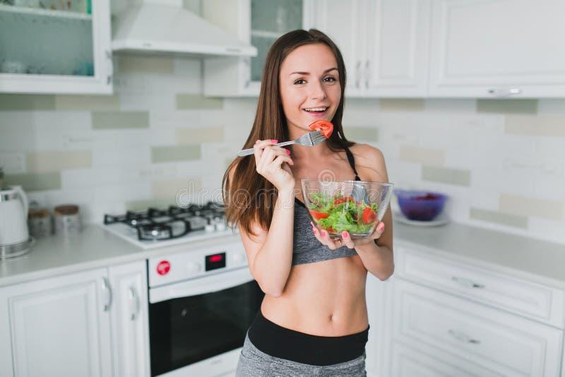 Meisje die en salade in de keuken voorbereiden eten royalty-vrije stock foto's