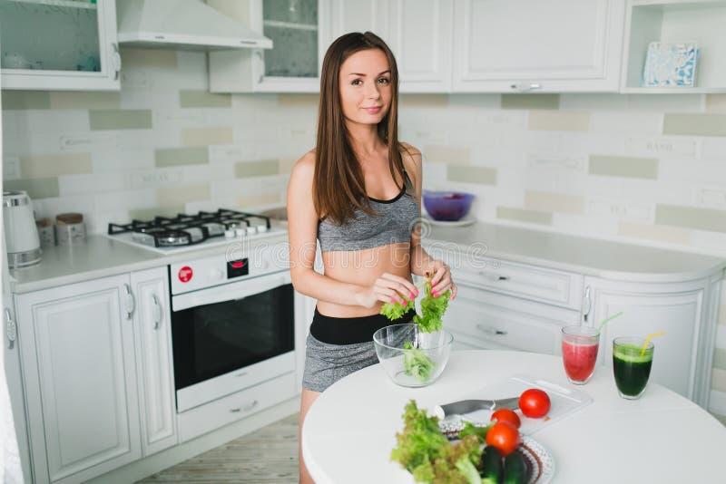 Meisje die en salade in de keuken voorbereiden eten royalty-vrije stock afbeeldingen
