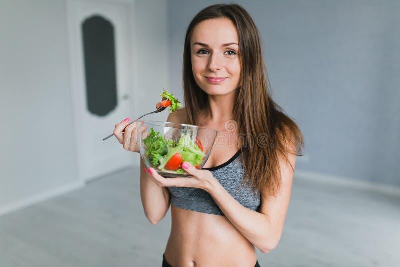 Meisje die en salade na geschiktheid opleiding voorbereiden eten royalty-vrije stock fotografie