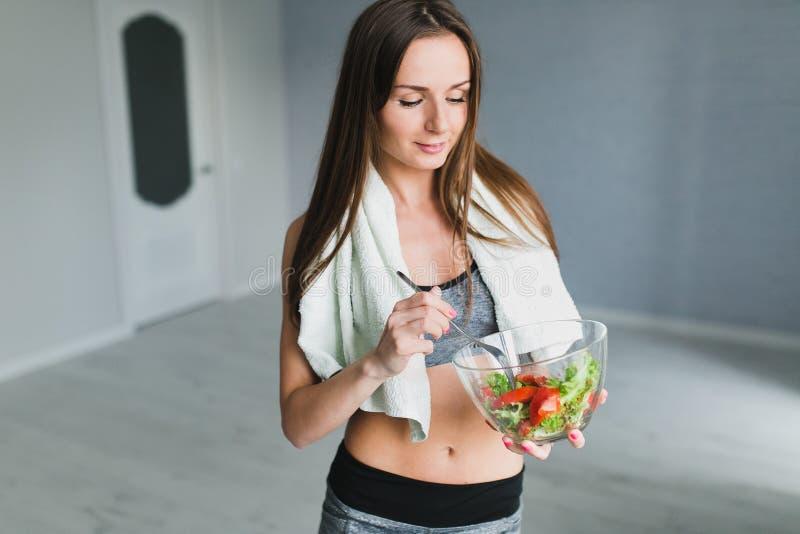 Meisje die en salade na geschiktheid opleiding voorbereiden eten stock fotografie