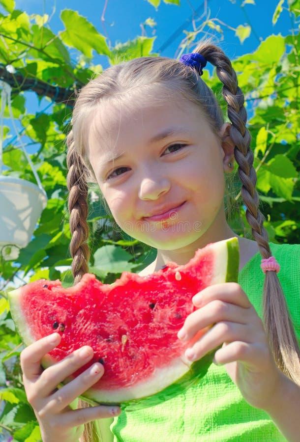Meisje die etend watermeloen stellen