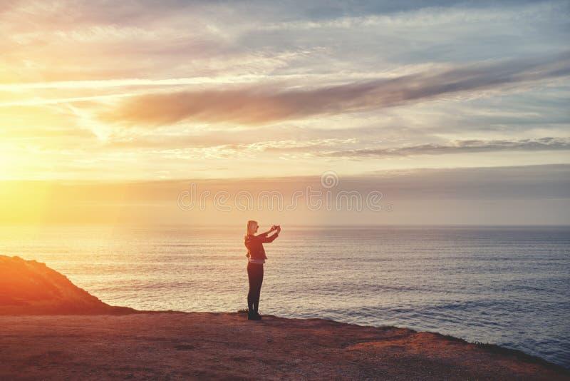 Meisje die foto met mobiele telefooncamera nemen terwijl status op bergheuvel tegen verbazende oceaan en zonsondergangachtergrond stock afbeeldingen